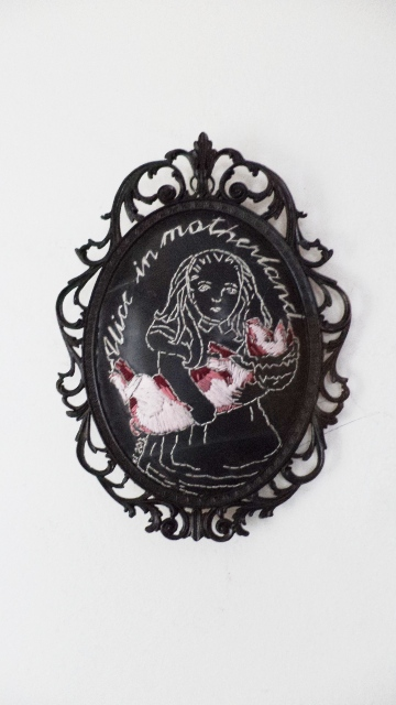 Alice in motherland, embroidery on rubber/inner tube and found frame